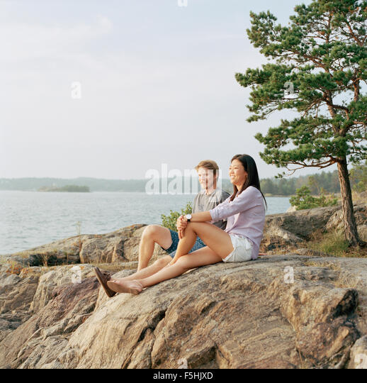 Sweden, Stockholm Archipelago, Sodermanland, Nacka, Mid-adult couple sitting on rocks, looking at sea - Stock Image