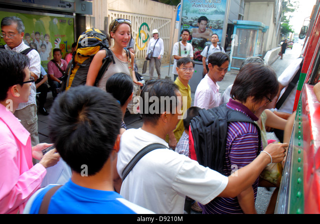 Bangkok Thailand Silom Rama IV Road public bus passengers entering Asian man - Stock Image