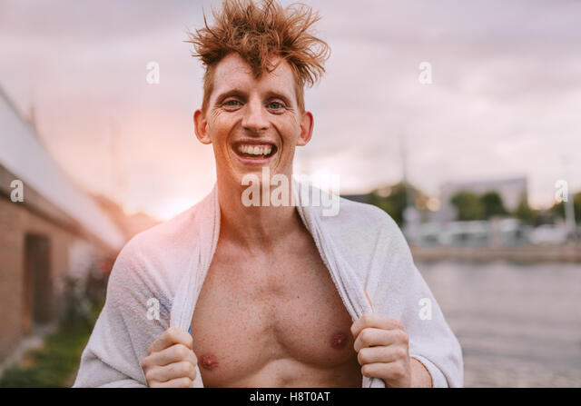 Portrait of handsome young man wrapped in towel looking at camera and smiling. Cheerful caucasian male model standing - Stock Image