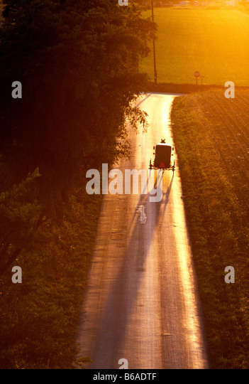 Aerial view of Amish horse drawn buggy on a rural road at sunset, Lancaster County, Pennsylvania, USA - Stock Image
