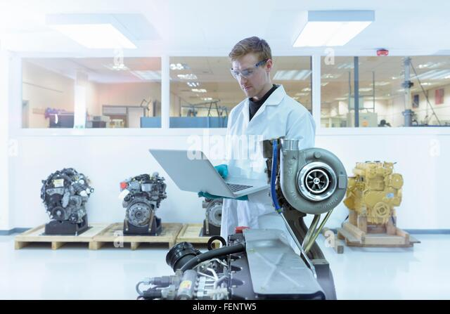 Scientist using laptop in turbo charger automotive research laboratory - Stock-Bilder