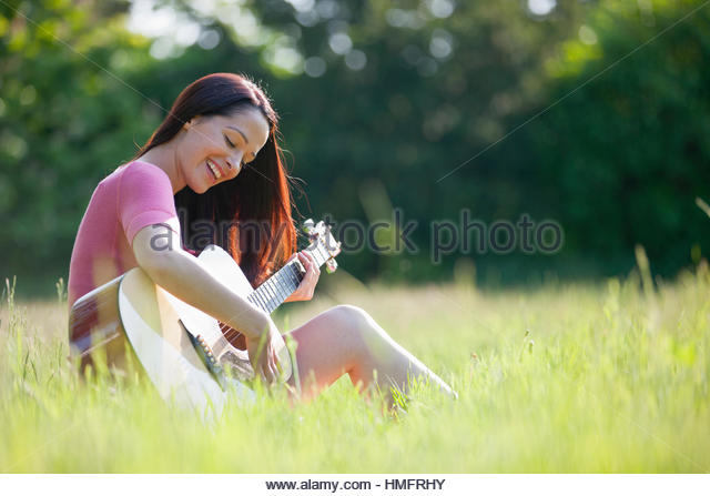 Happy woman playing guitar in sunny summer rural grass - Stock-Bilder