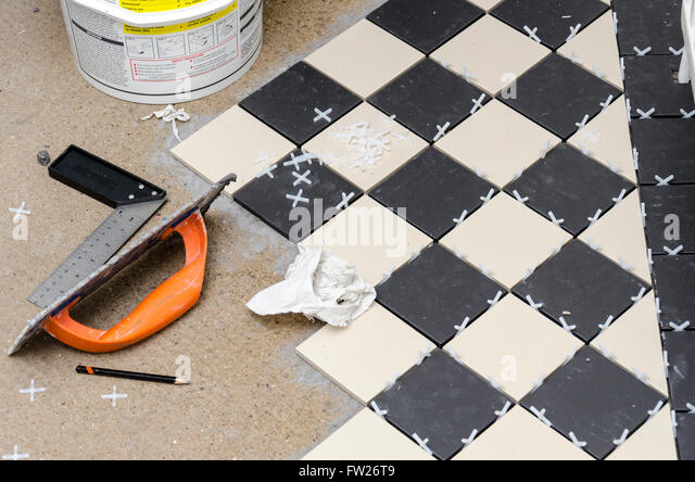 DIY laying a tile floor at home - Stock Image