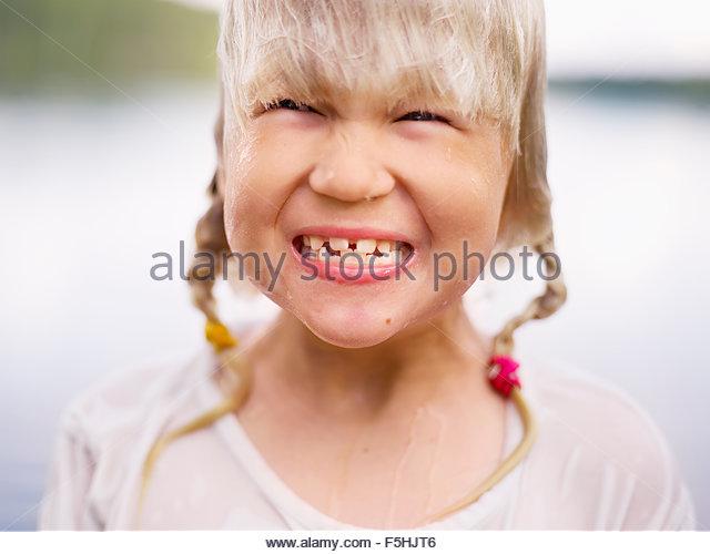 Sweden, Stockholm Archipelago, Uppland, Arholma, Portrait of girl (6-7) smiling - Stock Image