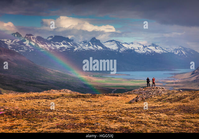 Two photographers takes picture in a light rain and rainbow in the Icelandic mountains. Colorful summer morning - Stock Image
