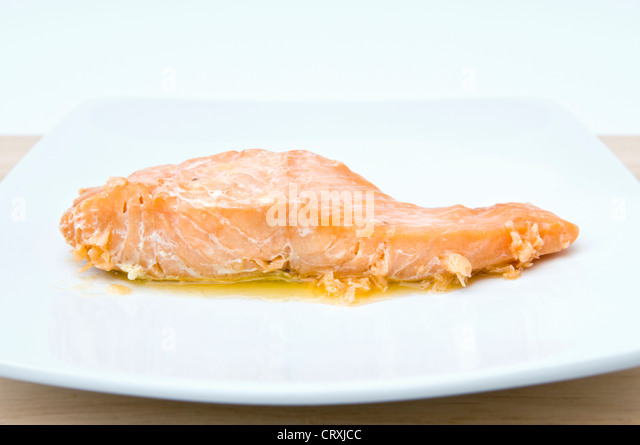 Cooked salmon with melted butter on white plate - Stock Image
