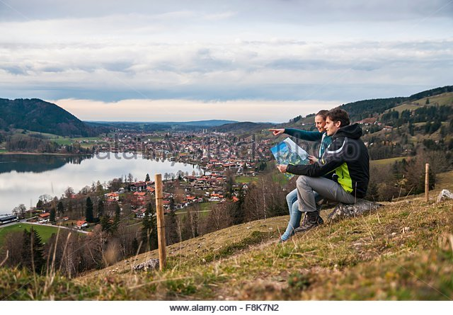 Side view of couple sitting looking at view of lake, holding map, Schliersee, Bavaria - Stock-Bilder