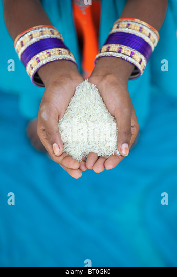 Indian girl holding uncooked rice in her cupped hands. India - Stock Image