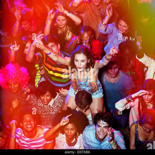 Cheering woman on manÍs shoulders at music festival - Stock-Bilder