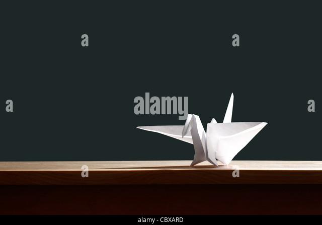 Origami bird on desk - Stock Image