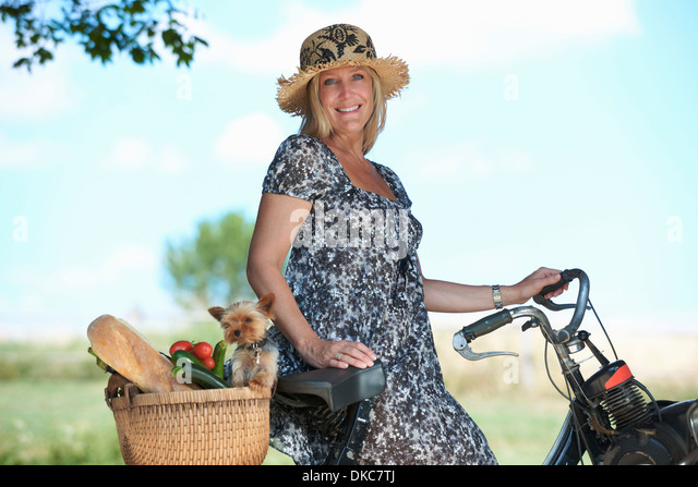 Mature woman on electric bike with dog and vegetables in basket - Stock-Bilder