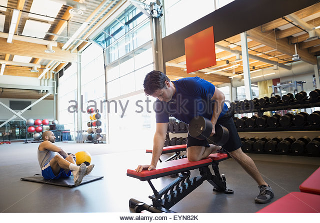 Man doing dumbbell rows on bench at gym - Stock Image