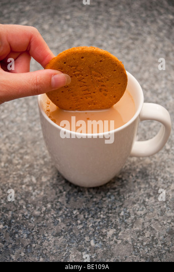 A close up of a person dunking a mcvities digestive biscuit in a cup of tea - Stock-Bilder