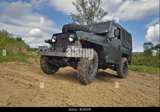 A 1960s Land Rover Lightweight Series 2a with headlamps in the radiator panel driving off road in Bining, France. - Stock Image