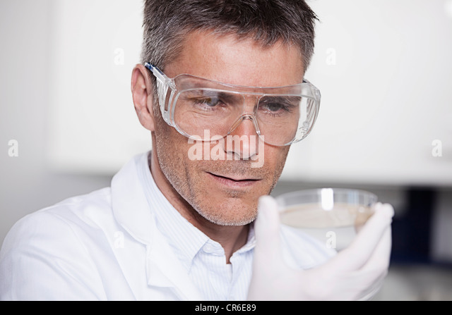 Germany, Bavaria, Munich, Scientist holding liquid in petri dish for medical research in laboratory - Stock Image