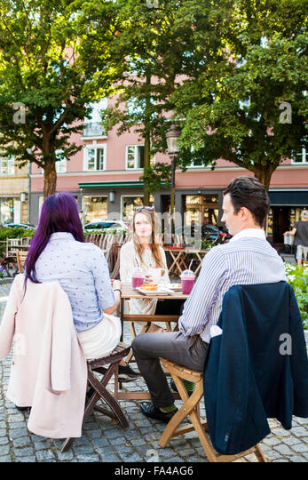 Friends talking at sidewalk cafe in town square - Stock Image