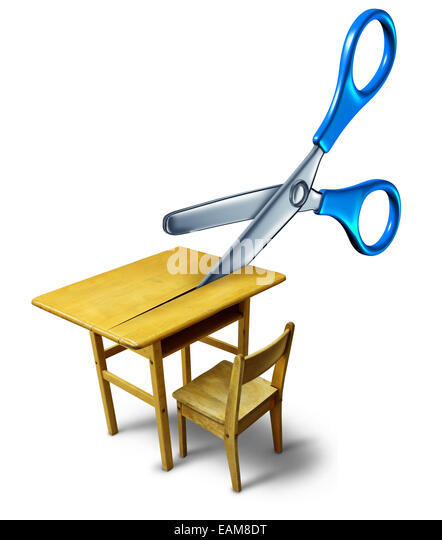School budget cuts crisis concept and education cutbacks symbol as an old class desk being cut by scissors as a - Stock Image