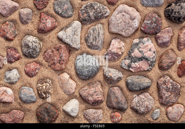 dry colourful stones arranged on sand as background - Stock Image