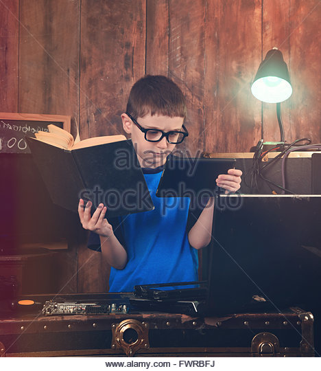 A boy is reading a science book and holding an internet tablet with computer objects around him for an education - Stock Image