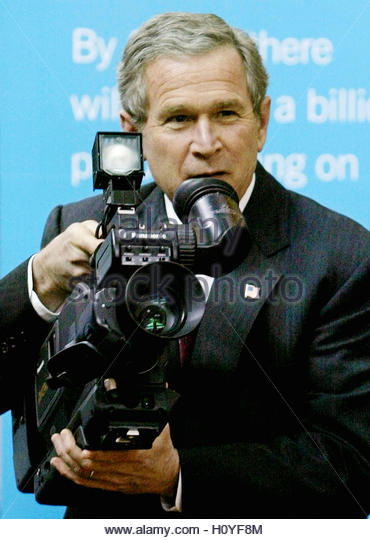 U.S. President George W. Bush looks at a camera powered by hydrogen fuel cells at the National Building Museum in - Stock Image