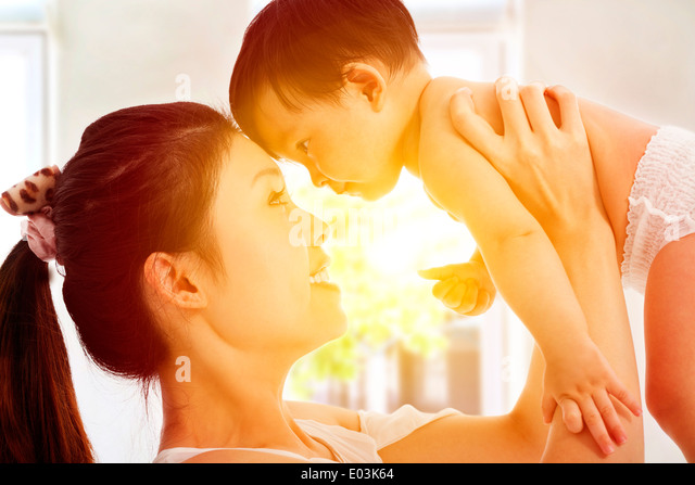 Happy mother holding adorable child baby with sunrise background - Stock Image