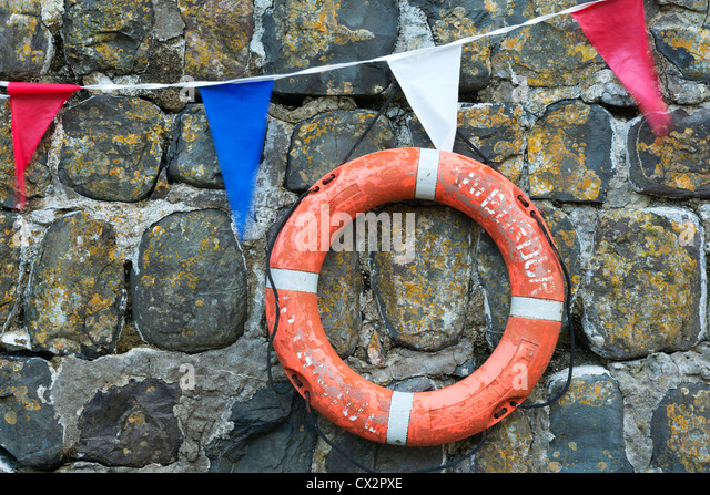 Life ring and bunting on the old harbour wall at Clovelly, Devon, England. Summer (August) 2012. - Stock Image