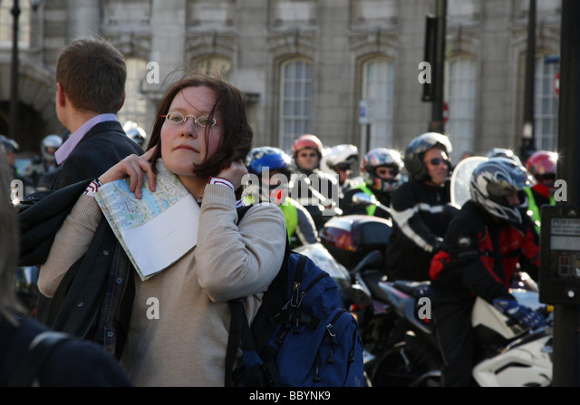 Woman blocks her ears from the sound of motorcycles revving. This was taken on the day of a protest by motorcyclists - Stock Image