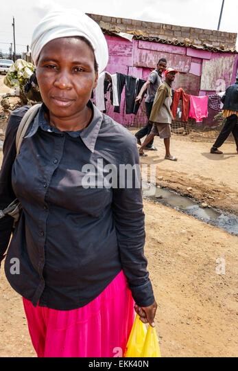 South Africa African Johannesburg Soweto Black woman resident street dirt - Stock Image