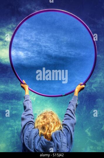 Girl holding up hula hoop with a grunge background and untreated sky in hoop - Stock-Bilder