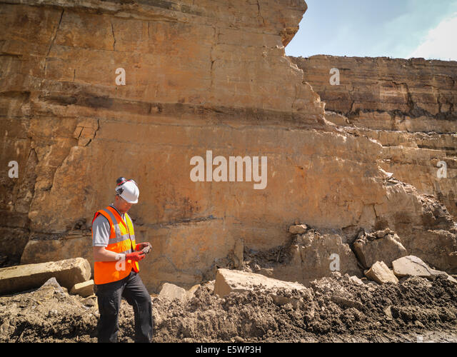 Quarry worker inspecting stone in quarry - Stock Image