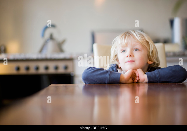 boy looking over table edge - Stock Image