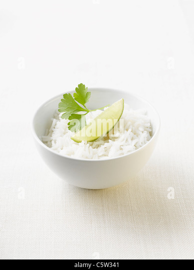 Boiled rice, garnished with parsley and lime in bowl - Stock Image