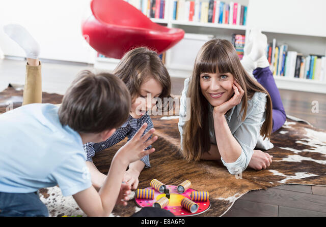 Mother playing board game with her children - Stock Image
