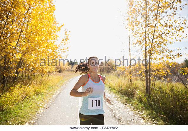 Runner racing on sunny autumn path - Stock Image