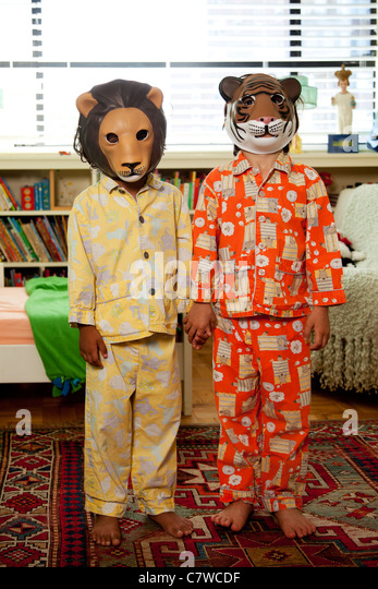 Two kids with masks on in pajamas - Stock Image