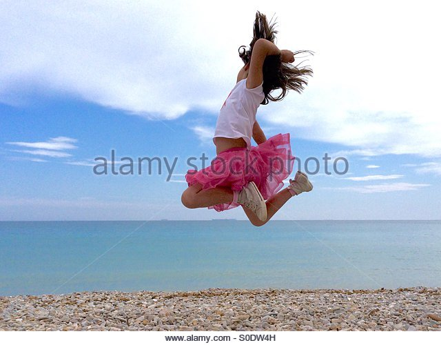 Girl caught in the air while  jumping by the Mediterranean Sea with pink skirt - Stock-Bilder