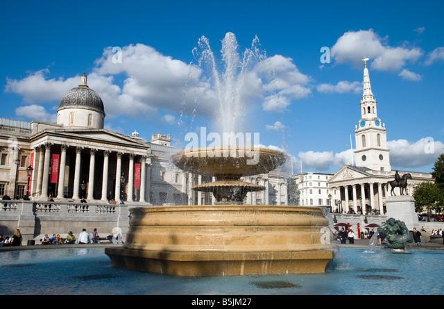 Water fountain in Trafalgar Square, London England UK - Stock Image