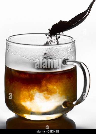 Adding the instant coffee to a cup of boiling hot water - Stock Image