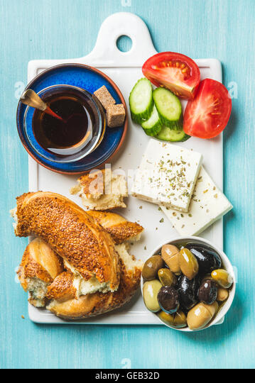 Turkish traditional breakfast with feta cheese, vegetables, olives, simit bagel and tea - Stock Image