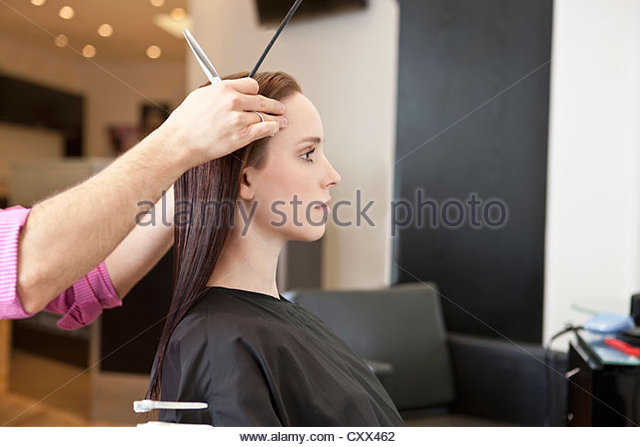 A female client looking in a mirror at a hairdressing salon whilst she is having her hair cut - Stock Image