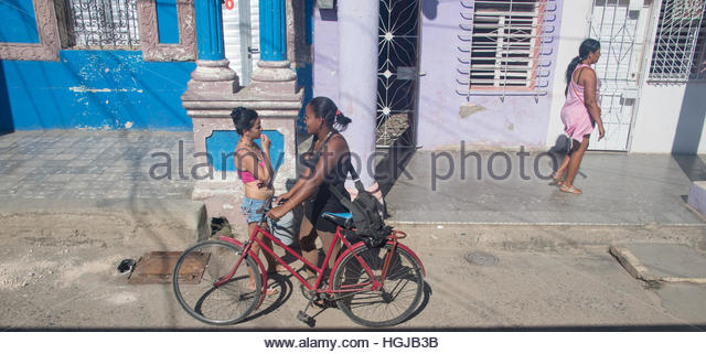 Real Cuban people lifestyle. Women talking with bicycle in front of a building. Another person walking on footpath - Stock-Bilder
