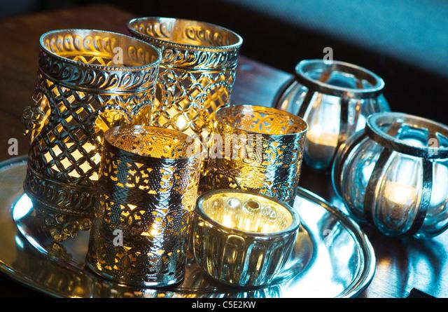 Close-up of several illuminate metal votives - Stock Image