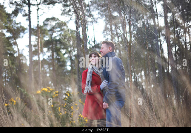 A young couple on a walk in the woods - Stock Image