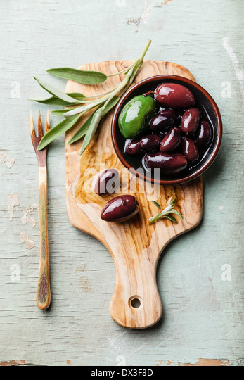 Olives with sage leaves on wooden background - Stock Image