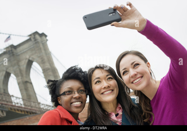 New York city the Brooklyn Bridge East River Three women in a row smiling as one takes a picture with a smart phone - Stock Image