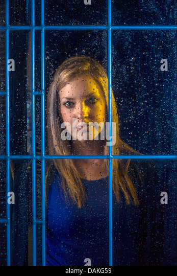 A teenage girl looks out a window on a rainy night with a serious expression in Laguna Beach, CA. - Stock Image