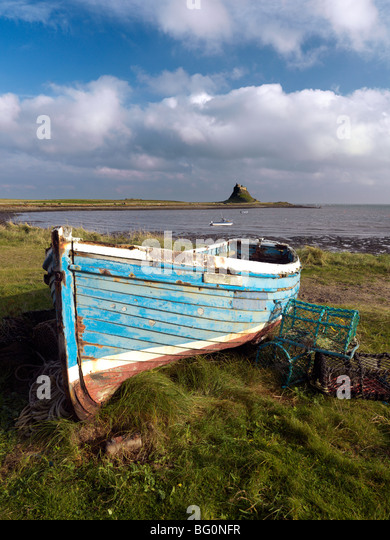 View towards Lindisfarne Castle with old fishing coble and lobster pots, Holy Island, Northumberland, England, United - Stock-Bilder