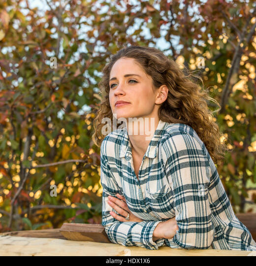 Caucasian woman leaning on wooden fence - Stock Image