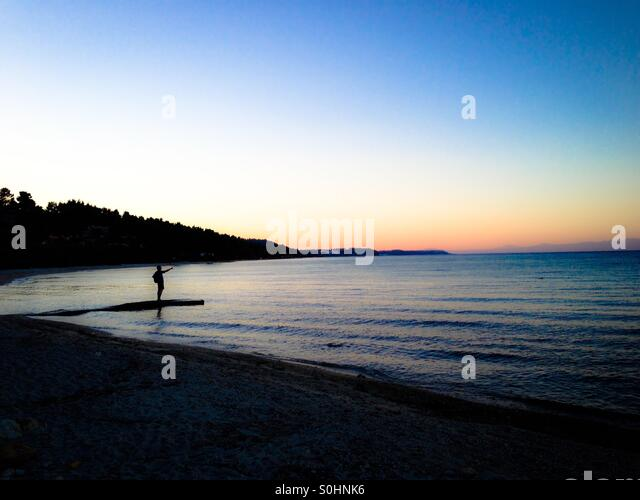 Man on jetty pointing out to sea at sunset over still water - Stock-Bilder