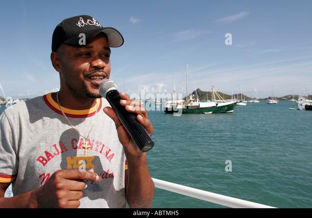 Saint Martin Simpson Bay Lagoon French Explorer Tour Boat Black male singer microphone - Stock Image